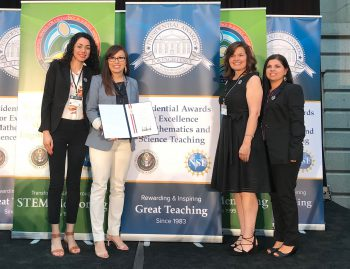 gabriela cardenas and colleagues posing with award at ceremony