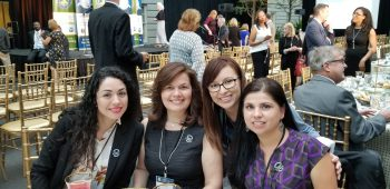 four women gathered at awards dinner and smiling in camera
