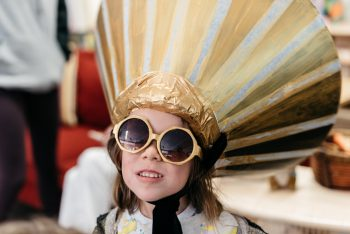 young child wearing sunglasses and headpiece made of castoff lampshade painted gold and silver