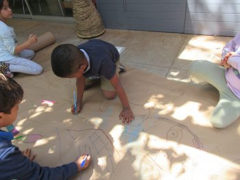 four young children drawing on large butcher paper laid out on a patio