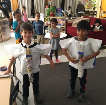 young children modeling shirts and ties made of butcher paper and newspaper