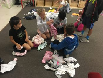 young children sitting on rug sorting donated clothing