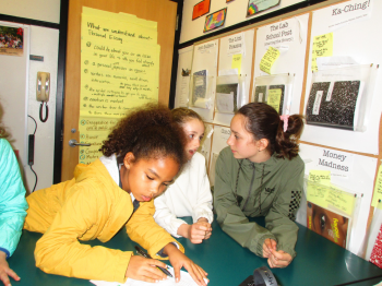 three girls meeting as a committee in a classroom