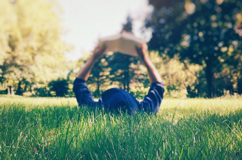 child outdoors reading book