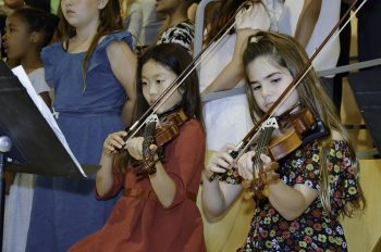 two girls playing violins