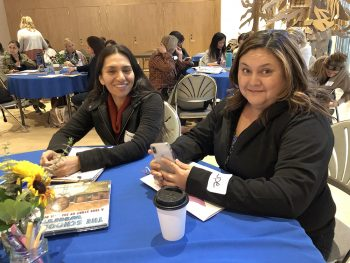 two teachers at table attending conference